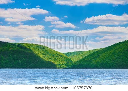green hills on the bank of the river. River landscape and beautiful blue sky with white clouds
