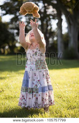 Little Girl Throwing Teddy Bear In The Air