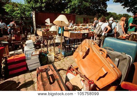 Leather Bags And Utensils On Sale With A Crowd Of Shoppers