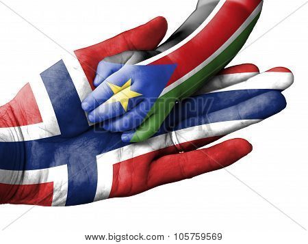 Adult Man Holding A Baby Hand With Norway And South Sudan Flags Overlaid. Isolated On White