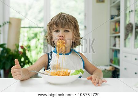 Little boy eating pasta