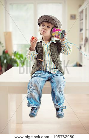 Little boy playing with tincan telephone