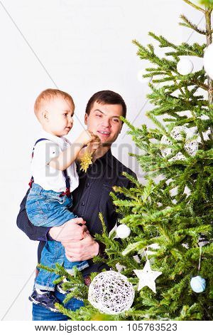 Happy father and son decorate Christmas tree