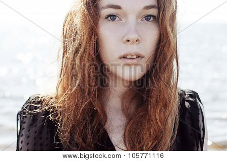 Young redhead woman outdoors portrait on  background of the sea.  Soft sunny colors.