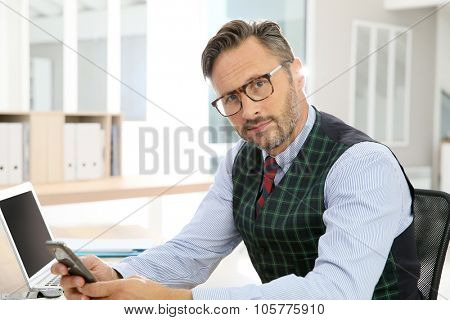Stylish man with eyeglasses sitting in office