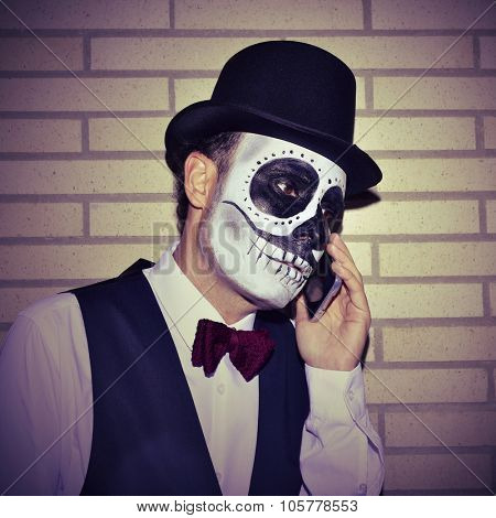 portrait of a man with mexican calaveras makeup, wearing bow tie and top hat, on the phone