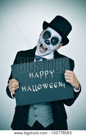 a man with mexican calaveras makeup, wearing jacket, vest, bow tie and top hat, shows a signboard with the text happy halloween