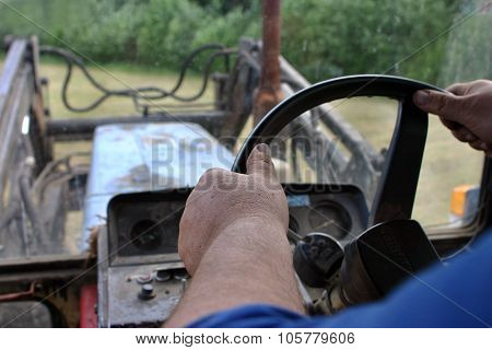 Closeup Of  Hand Farmer Tractor-driver On Tractor Steering Wheel.