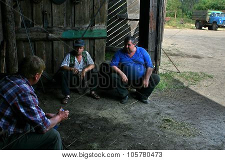 Three Men, Farm Workers Talking In Shade Of Wooden Barn.