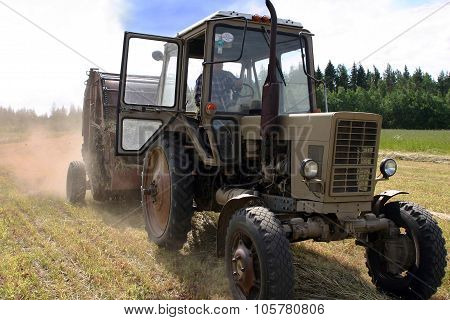 Farm Wheeled Tractor With Round Hay Baler On New-mown Meadow.