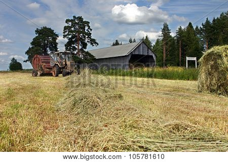 Russian Farmland, While Hay, Tractor Round Baler Works In Hayfield.