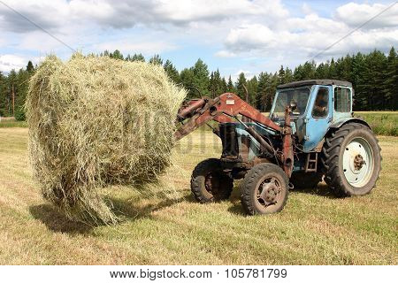 Russian Farm Tractor Moves Round Bales Of Hay.