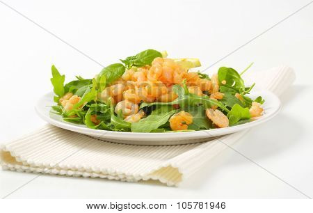 plate of shrimp and greens salad on white place mat