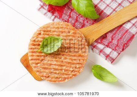 raw burger patty with basil on wooden spatula