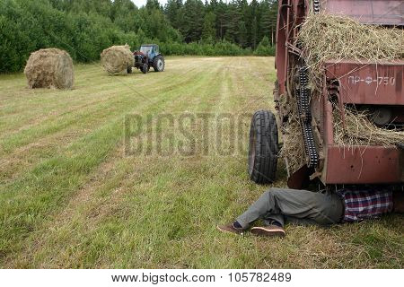 Driver Of Tractor Repair Round Baler In The Field.