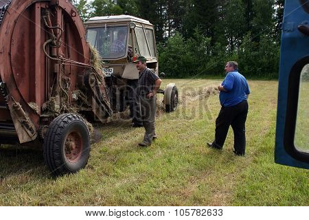 Tractor Farm Equipment Mechanics Inspect In Process Of Making Hay.