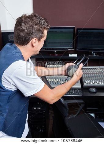 Side view of young man holding headphones while sitting at mixing table in recording studio