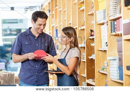 Smiling saleswoman showing greeting cards to male customer in shop