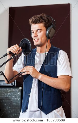 Young man singing while holding microphone in recording studio