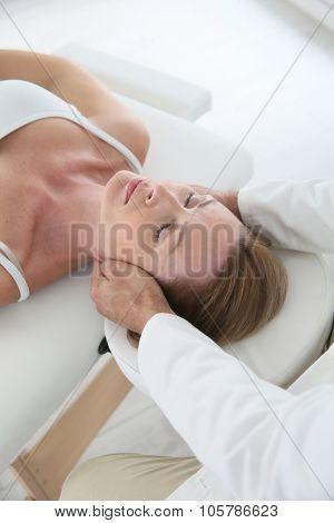 Chiropractor touching woman's head