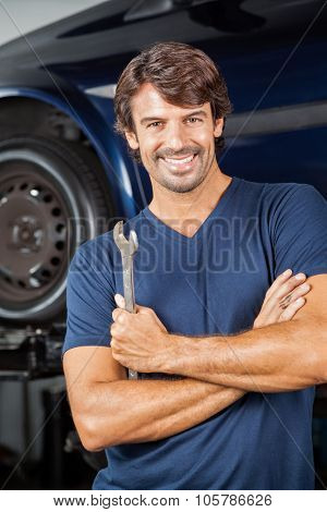 Portrait of smiling mechanic holding wrench while standing arms crossed at repair shop