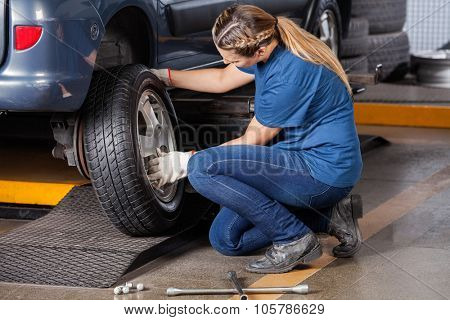Side view of female mechanic replacing car wheel at auto repair shop