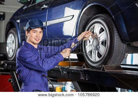 Portrait of confident male mechanic filling air into car tire at garage