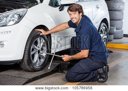 Side view portrait of male mechanic fixing car tire with rim wrench at garage