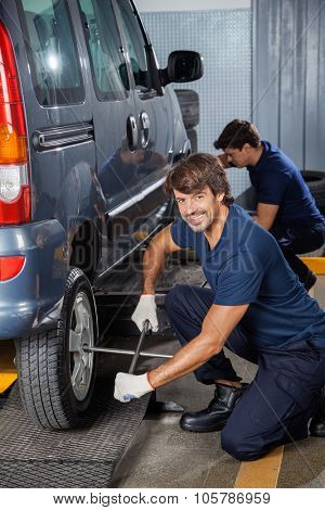 Portrait of smiling male mechanic fixing car tire with rim wrench at auto repair shop