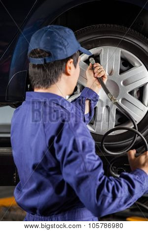 Young male mechanic filling air in car tire at auto repair shop