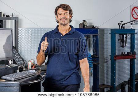 Portrait of happy mechanic gesturing thumbsup at auto repair shop
