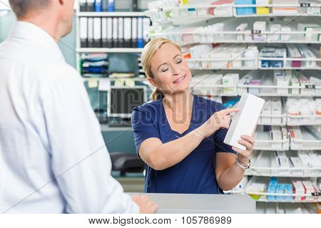 Smiling female pharmacist showing details of product to customer in pharmacy