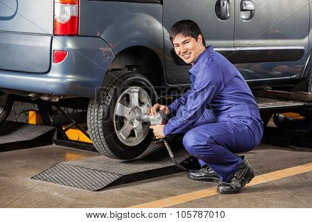 Side view portrait of happy mechanic fixing car tire pneumatic wrench at garage