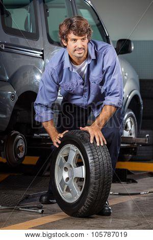 Male mechanic holding car tire at auto repair shop