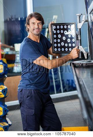 Smiling male mechanic looking away while adjusting wheel aligner on car in garage