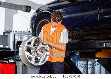 Male mechanic examining metallic alloy at auto repair shop