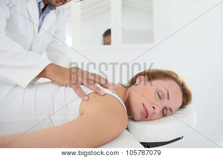 Chiropractor checking woman's spine
