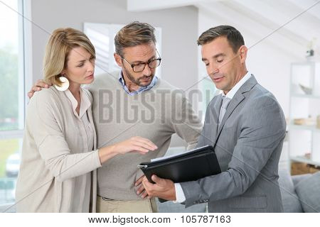 Real-estate agent showing house details on paper
