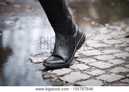 female leg in black  leather high boots on cobble on the edge of rain puddle, closeup, selective focus,