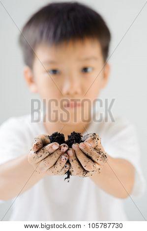 Boy carries black soil