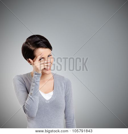 Beautiful young woman covers her eyes with hand, isolated on grey