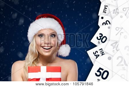 Pretty woman in Christmas cap hands present wrapped with red paper, on blue background. Winter sale