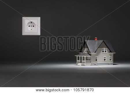 Home architectural model with socket on grey background