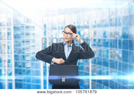 Portrait of business woman keeping case, blue background. Concept of leadership and success