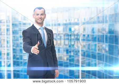 Portrait of businessman hand shake gesturing, blue background