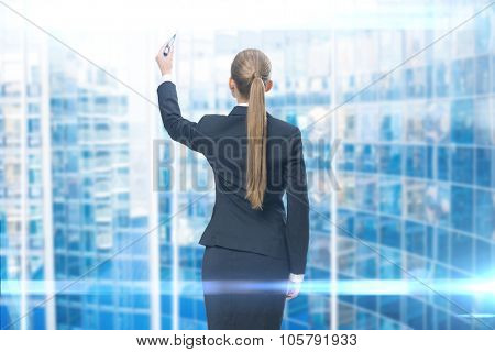 Backview of businesswoman writing on blue screen. Concept of leadership and success