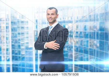 Portrait of business man with hands crossed, blue background. Concept of leadership and success