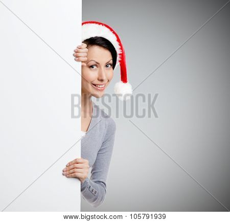 Pretty smiley woman peeps out through the wall, wearing Christmas red cap, isolated on grey