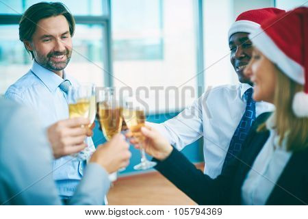Multi-ethnic business people with champagne celebrating Christmas at office party