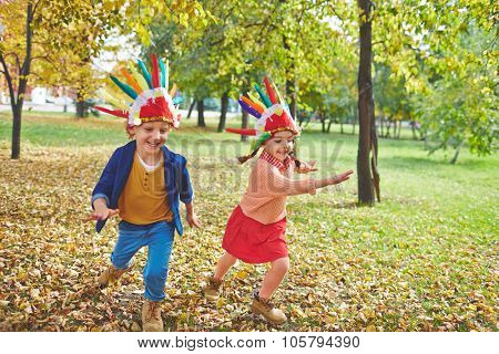 Cute girl and boy in Indian headdresses running in autumn park